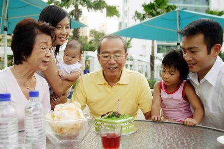 three generation: Three generation family celebrating grandfathers birthday