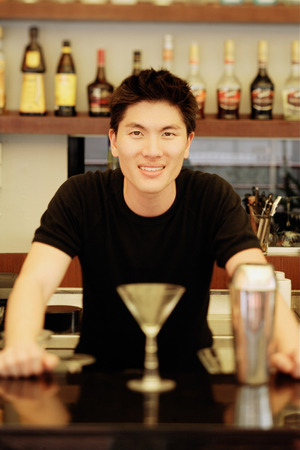 cocktail mixer: Man behind bar counter, glass and mixer in front of him