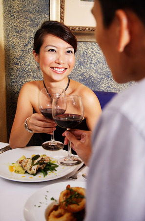 Couple in restaurant toasting with wine glasses
