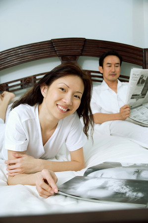 Couple in bedroom, woman smiling at camera, man reading newspaper in the background