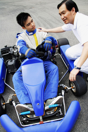 crouching: Young man in go-cart, father crouching down next to him