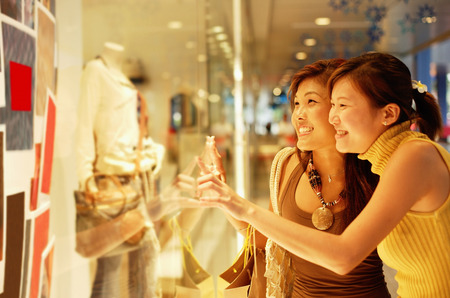 Young women, standing outside window display, looking in Stock Photo