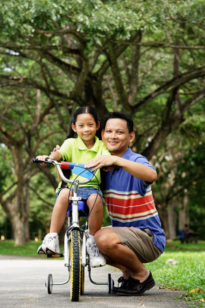 crouching: Girl on bicycle, father crouching down next to her, both looking at camera