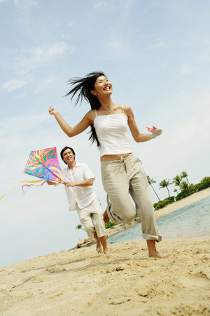 Couple flying kite along beach, woman running in front of man
