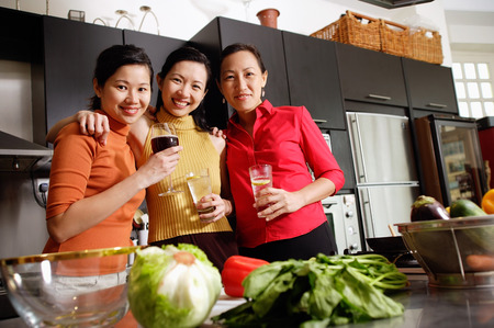 Women in kitchen, standing side by side, smiling at camera LANG_EVOIMAGES