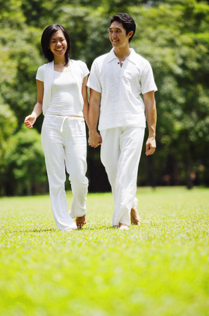 Couple walking hand in hand in park Stock Photo