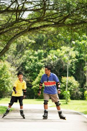 skate park: Father and son in park, on roller blades LANG_EVOIMAGES