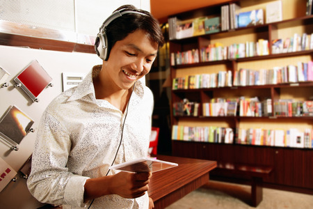 Young man listening to music, smiling, looking down at CD Stock Photo