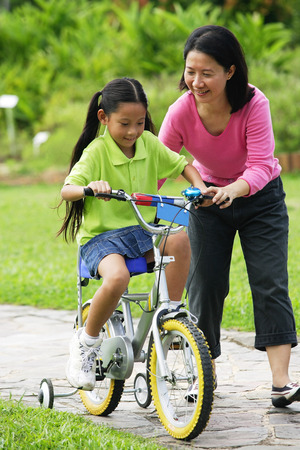 Young girl cycling, mother guiding her