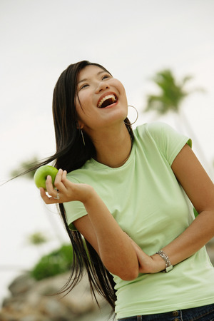 Woman holding apple, laughing, looking away