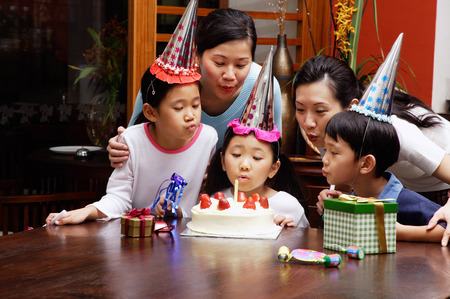Family celebrating birthday, blowing candle LANG_EVOIMAGES
