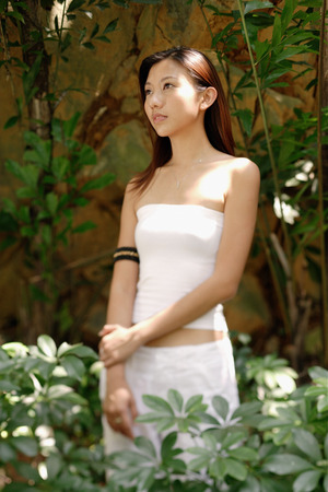 Young woman standing and looking away, plants around her