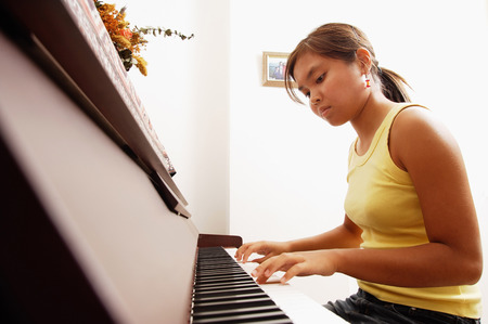 looking down: Young woman sitting at piano, looking down LANG_EVOIMAGES