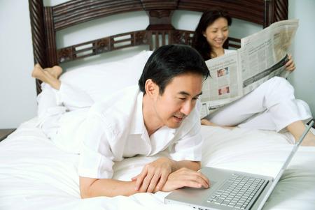 新聞を読んで女性のラップトップを使用している人の寝室でカップル 写真素材