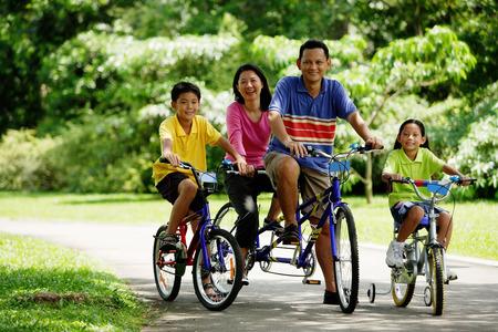 公園、自転車、カメラ目線の家族 写真素材