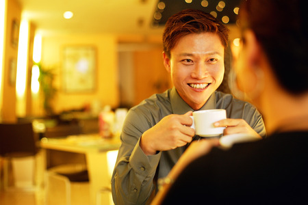 Couple in restaurant, man holding cup, facing woman, over the shoulder view LANG_EVOIMAGES