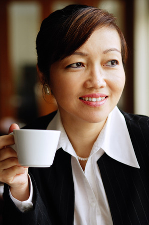 Businesswoman holding cup, looking away Stock Photo