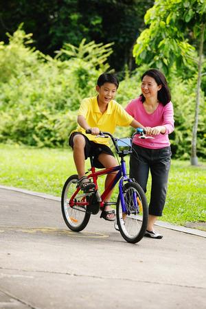自転車、彼の隣に母の息子