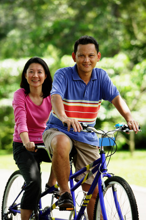 Couple on tandem bicycle, looking at camera LANG_EVOIMAGES
