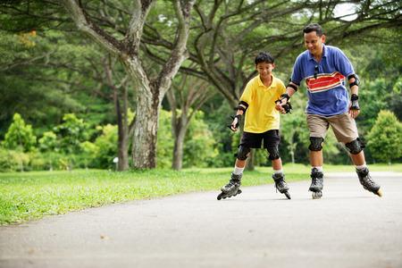 父と息子、インライン スケート公園で手をつないで