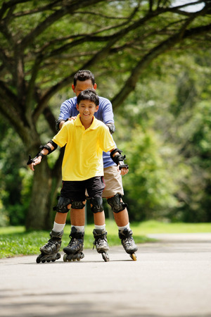hair roller: Father and son, in-line skating in park, father holding son from behind LANG_EVOIMAGES