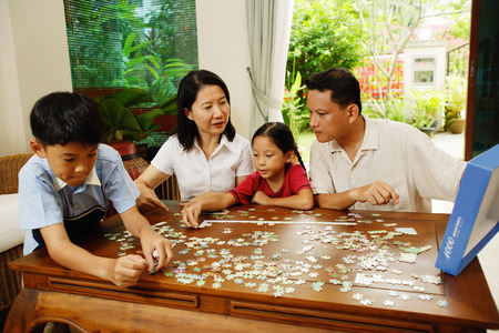 family  room: Family in living room, playing jigsaw puzzle