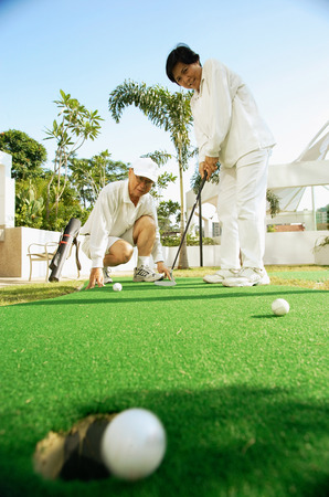 crouching: Senior couple playing golf, woman with golf club, man crouching down LANG_EVOIMAGES