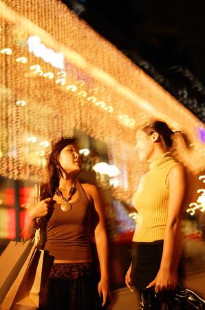 サイド バイ サイド、携帯用ショッピング バッグを歩く若い女性