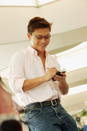 personal digital assistant: Man using PDA, looking down