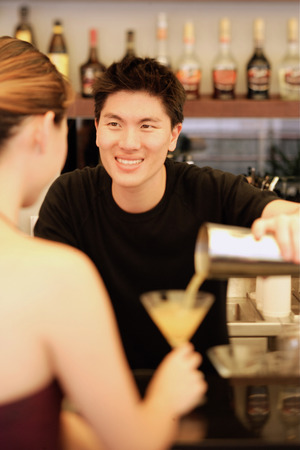 cocktail mixer: Man holding cocktail mixer, pouring drink for woman LANG_EVOIMAGES