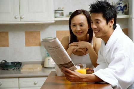 キッチン、朝食を食べて、新聞を見てのカップル 写真素材
