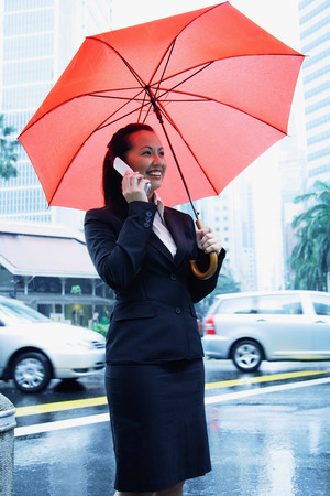 Business woman using mobile phone, holding umbrella Stock Photo