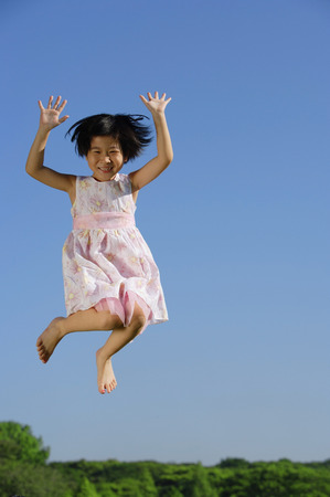 mid air: Girl in pink dress, jumping in mid air, smiling at camera