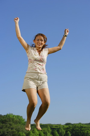 mid air: Woman jumping in mid air, smiling at camera LANG_EVOIMAGES