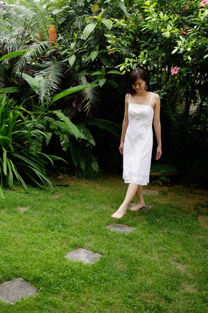 stepping: Woman in white dress stepping on stones in garden LANG_EVOIMAGES