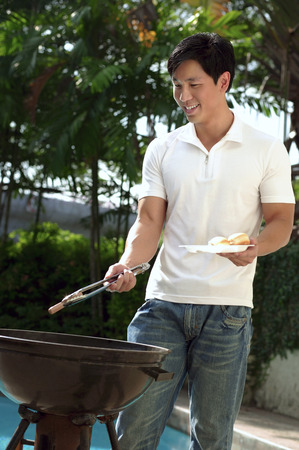 Young man having a barbeque