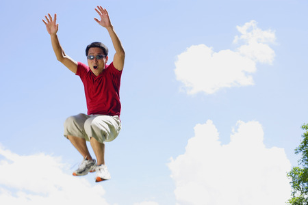 mid air: Man jumping in mid air, arms outstretched, mouth open