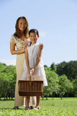 Mother and daughter in park, looking at camera, girl holding picnic basket