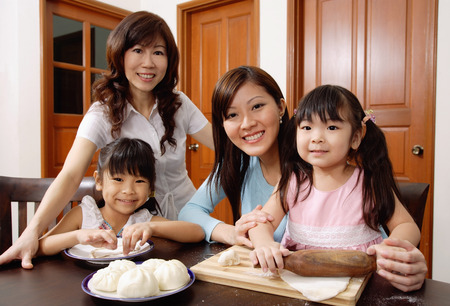 three generations: Three generations of females, in kitchen, smiling at camera LANG_EVOIMAGES