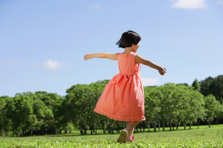 Girl in peach dress, walking on grass, arms outstretched