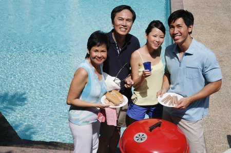 Family enjoying barbeque by the pool