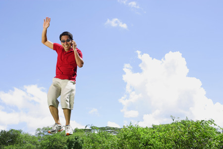 mid air: Man jumping in mid air, holding mobile phone