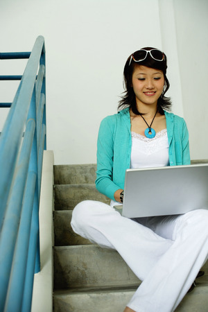 Woman sitting on stairs, using laptop