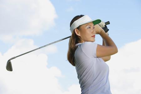 woman golf: Woman wearing sun visor, swinging golf club LANG_EVOIMAGES