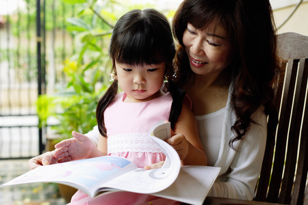 Grandmother and granddaughter looking at book Stock Photo