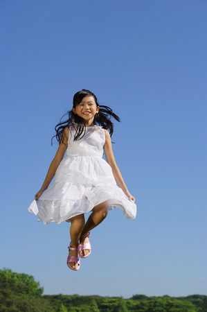 mid air: Girl wearing white dress, jumping in mid air