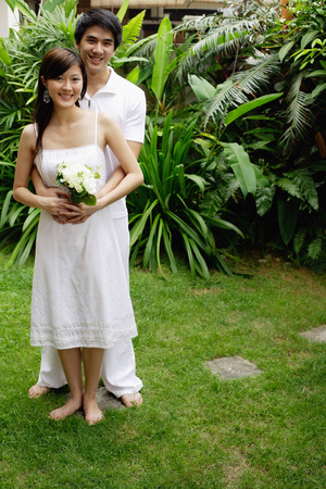 Couple in garden, man with arms around woman, woman holding bouquet Stock Photo