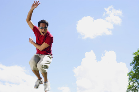 mid air: Man jumping in mid air, hand raised, mouth open