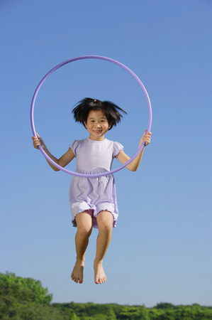 mid air: Girl in lavender dress, jumping in mid air, holding hoop