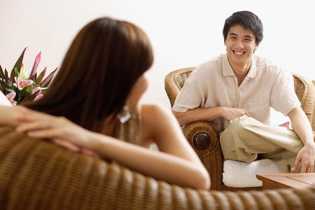 Couple at home in living room, woman turning to look at man Stock Photo